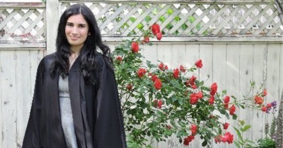 Serena Bains, Youth Leadership Initiative Coordinator, posing in garden with graduation gown on.