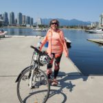 Celia standing with a bicycle by the water at Creekside