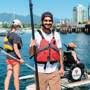Sahil standing on BCMOS Paddling dock, wearing a life jacket and holding a paddle.
